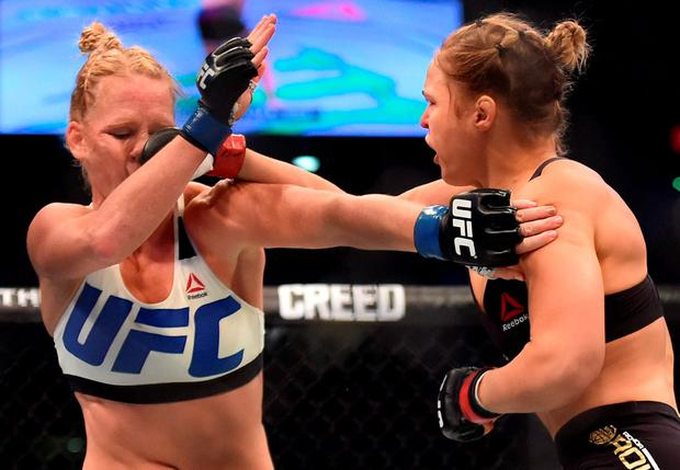 Ronda Rousey of the US (R) lands a punch on the face of compatriot Holly Holm during the UFC title fight in Melbourne on November 15, 2015. RESTRICTED TO EDITORIAL USE NO ADVERTISING USE NO PROMOTIONAL USE NO MERCHANDISING USE. AFP PHOTO/Paul CROCKPAUL CROCK/AFP/Getty Images