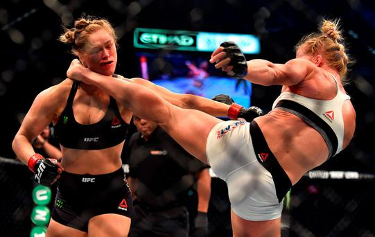 Holly Holm of the US (R) lands a kick to the neck to knock out compatriot Ronda Rousey and win the UFC title fight in Melbourne on November 15, 2015. RESTRICTED TO EDITORIAL USE NO ADVERTISING USE NO PROMOTIONAL USE NO MERCHANDISING USE. AFP PHOTO/Paul CROCKPAUL CROCK/AFP/Getty Images