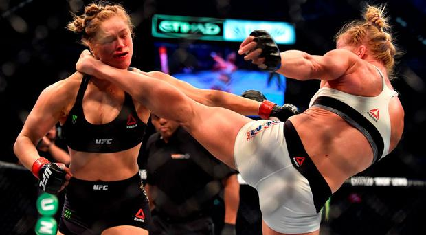 Holly Holm of the US (R) lands a kick to the neck to knock out compatriot Ronda Rousey and win the UFC title fight in Melbourne on November 15