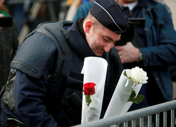A policeman crys as he places flowers outside the Bataclan concert hall the morning after a series of deadly attacks in Paris Credit: Charles Platiau (REUTERS)