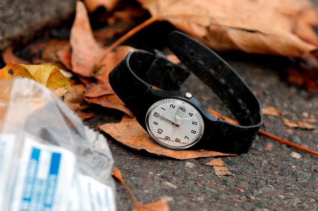 A watch lays on the ground outside the Bataclan concert hall Credit: Christophe Ena (AP)