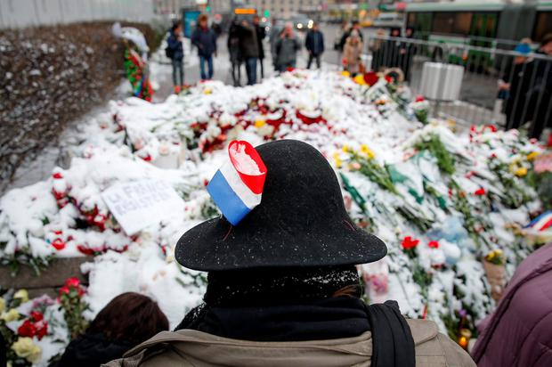 A woman with a ribbon in the colors of the French national flag attached to her hat stands next to flowers, laid to commemorate victims of attacks in Paris, near the French embassy in Moscow, Russia, November 15, 2015. REUTERS/Maxim Zmeyev