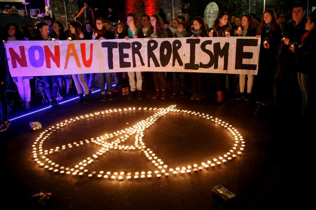 In this Saturday Nov. 14, 2015 picture people gather around a peace sign with Eiffel Tower, realized by candles, during a rally for the victims of the terrorist attacks in Paris, in Lausanne, Switzerland. Banner in French reads : No to terrorism. Multiple attacks across Paris on Friday night have left scores dead and hundreds injured. (Salvatore Di Nolfi/Keystone via AP)