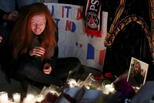 Polina Volkova, a friend of Eagles Of Death Metal's merchandise manager Nick Alexander (R in photograph), who died in attacks in Paris, cries as she sits near a makeshift memorial during a vigil outside the consulate of France in the Manhattan borough of New York November 14, 2015. REUTERS/Carlo Allegri