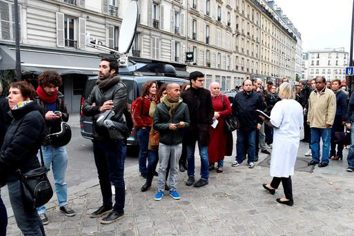 A queue of people wait to donate blood at the Hopital Saint Louis in Paris