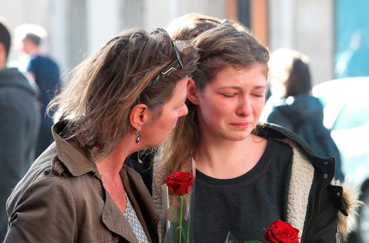 Passersby show emotion as they leave tributes at La Casa Nostra pizzeria, Paris, one of the venues for the attacks in the French capital