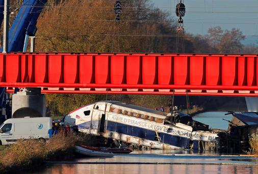 Workers use cranes to lift a carriage of a test TGV train that derailed, killing at least 11 people, in a canal outside Strasbourg