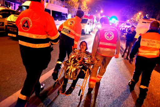 Rescue workers help a woman outside the Bataclan theatre