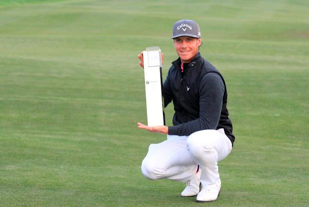 Kristoffer Broberg of Sweden poses with the trophy after winning the BMW Masters in Shanghai
