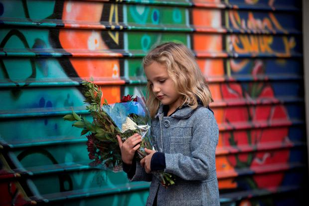 Zadig Jestin (6) lays flowers outside a restaurant in Paris yesterday