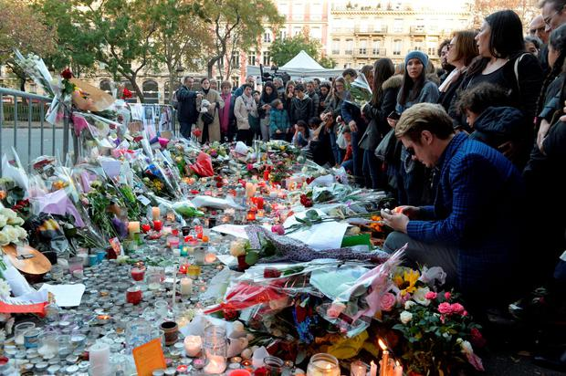 People mourn as they gather at a makeshift memorial near the Bataclan concert hall