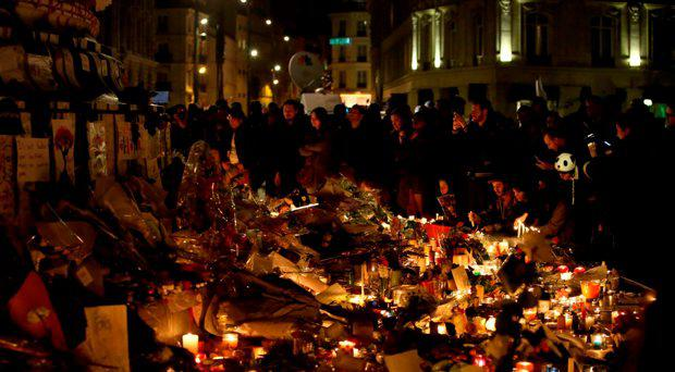 Crowds gather to look at floral tributes and candles left at Place de la Republique (Republic Square), following the terrorist attacks on Friday evening