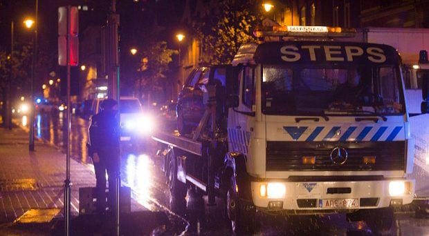 A car is towed during a police raid in Brussels' Molenbeek district on November 14, 2015