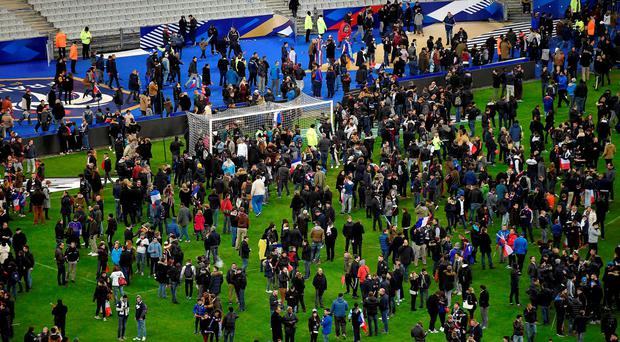 Football fans gather on the field of the Stade de France stadium following the friendly football match between France and Germany in Saint-Denis, north of Paris, on November 13, 2015, after a series of gun attacks across Paris as well as explosions outside the national stadium where France was hosting Germany. Three loud explosions were heard outside France's national stadium during the first half of a friendly international football match between France and Germany. At least four people died outside the glittering venue which staged the 1998 World Cup final with several others seriously hurt. AFP PHOTO / FRANCK FIFEFRANCK FIFE/AFP/Getty Images