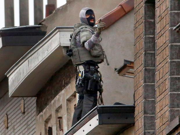 A Belgian special forces policeman gestures from high on an apartment block during a raid, in search of suspected muslim fundamentalists linked to the deadly attacks in Paris, in the Brussels suburb of Molenbeek, November 16. Reuters/Yves Herman