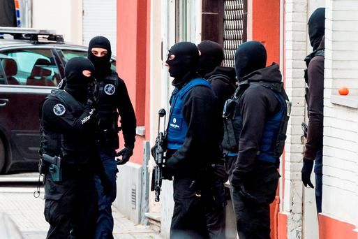 Armed police guard a street in Brussels on Monday, Nov. 16, 2015. A major action with heavily armed police is underway in the Brussels neighborhood of Molenbeek amid a manhunt for a suspect of the Paris attacks. (AP Photo/Geert Vanden Wijngaert)