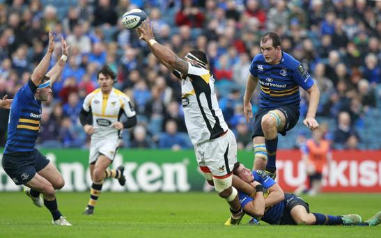 Wasps' Nathan Hughes offloads as he is tackled by Johnny Sexton of Leinster