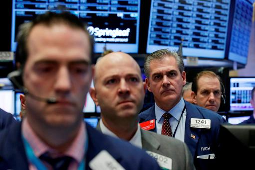 Traders on hold a moment of silence, in response to the Paris attacks, on the floor of the New York Stock Exchange. Photo: Reuters