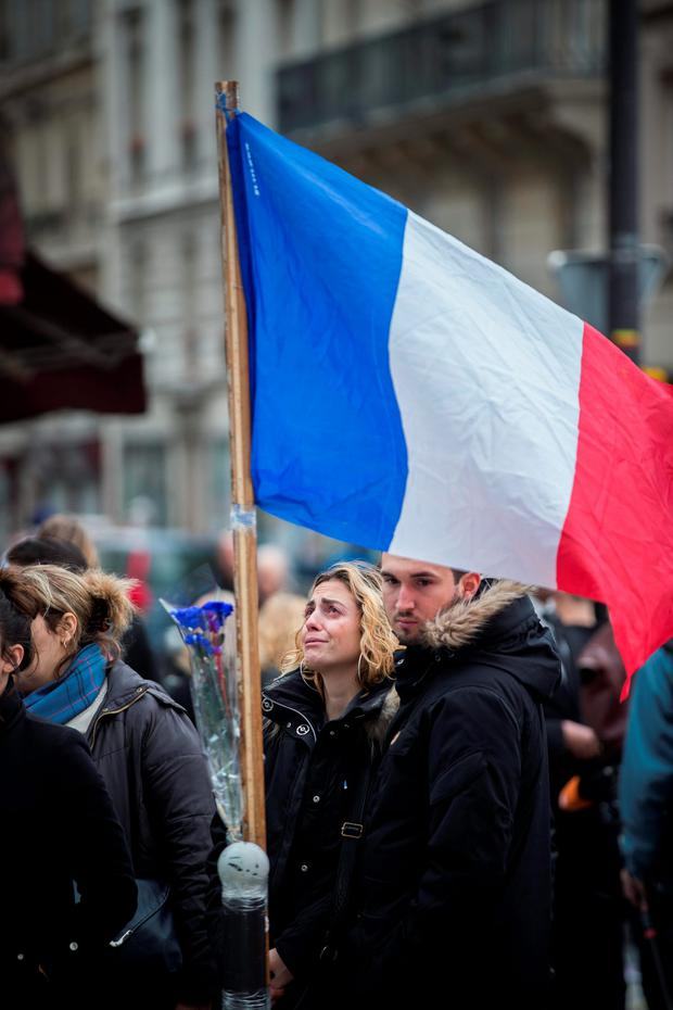 Mourners gather at the scene of one of the attacks in Paris