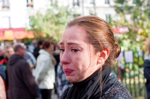 A mourner in tears outside the Le Carillon restaurant in Paris, where 129 lost their lives on Friday night. Photo: Mark Condren