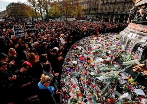 People observe a minute's silence at the Place de la Republique in memory of the victims
