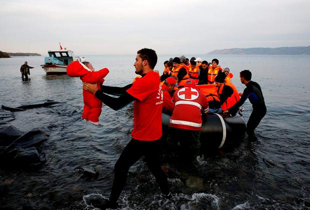 A Red Cross volunteer carries a Syrian refugee baby off an overcrowded raft at a beach on the Greek island of Lesbos Credit: Yannis Behrakis