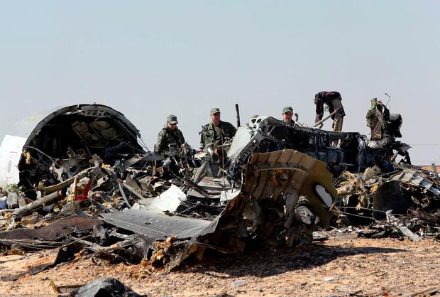 Military investigators from Russia stand near the debris of a Russian airliner at the site of its crash at the Hassana area in Arish city, north Egypt, in this November 1, 2015. Reuters/Mohamed Abd El Ghany/Files