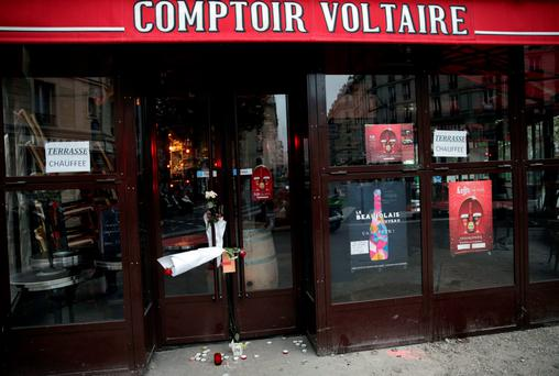Flowers are placed on the doors of the Comptoir Voltaire cafe at the site of an attack on November 15, 2015 in Paris, after a series of gun attacks occurred across the city. Photo: AFP/Getty Images