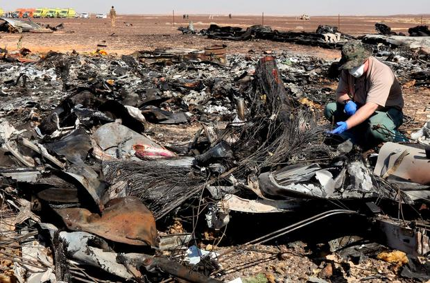 A military investigator from Russia stands near the debris of a Russian airliner at its crash site at the Hassana area in Arish city, north Egypt, November 1, 2015