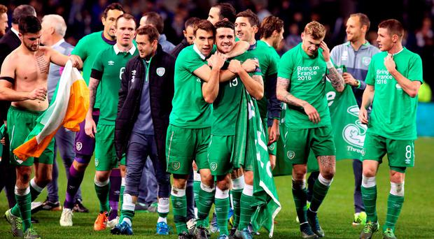 Republic of Ireland's Robbie Brady (C) gets a hug from Seamus Coleman after qualifying for the Euros