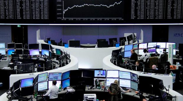 Traders work at their screens in front of the German share price index. Photo: Reuters