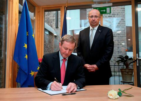 Taoiseach, Enda Kenny signs the book of condolence for the victims of the attacks in Paris with Ambassador Jean Pierre Thebault at the French Embassy in Dublin.