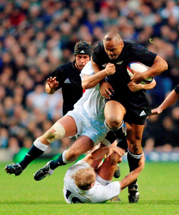 New Zealand's Jonah Lomu runs over England's Neil Back on the way to the try line during the All Blacks' match at Twickenham in London in 2002.