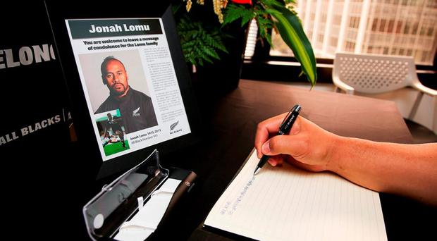 A well-wisher signs a condolence book at New Zealand Rugby Union headquarters following All Black legend Jonah Lomu's death.