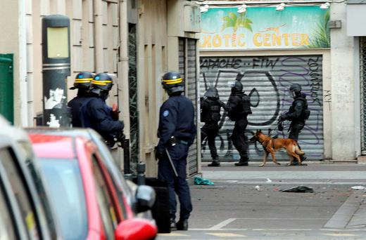 Members of special French RAID forces with a police dog and French riot police (CRS) secure the area during an operation in Saint-Denis, near Paris, France, November 18, 2015 to catch fugitives from Friday night's deadly attacks in the French capital. REUTERS/Philippe Wojazer