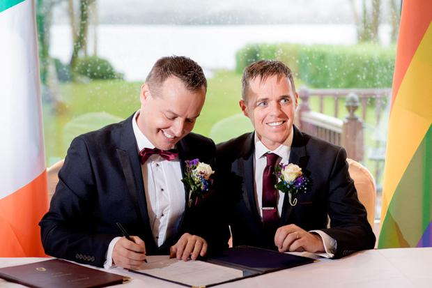 Wayne Gough (left) and DJ O'Hanlon (right) signing the register after their marriage yesterday Credit: Paul McGinty of Ghorm Photography