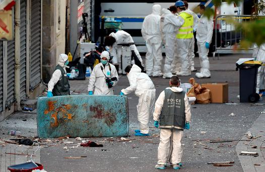 Forensics of the French police search for evidences outside a building in the northern Paris suburb of Saint-Denis