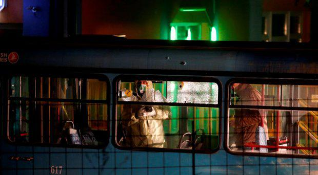 Bosnian policeman inspect inside of a public bus parked near building where an armed man killed soldiers, in the Sarajevo suburb of Rajlovac, Bosnia, Thursday, Nov. 19, 2015