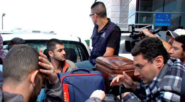 Syrian men sit in the bed of a truck after being detained at Toncontin international airport in Tegucigalpa, Honduras, November 18, 2015. Honduran authorities have detained five Syrian nationals who were trying to reach the United States using stolen Greek passports, but there are no signs of any links to last week's attacks in Paris, police said