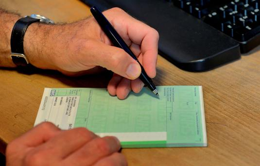 File photo: A doctor writing a prescription, as poorer dementia patients in England are less likely to be prescribed the drugs they need, according to new research. Photo: Anthony Devlin/PA Wire