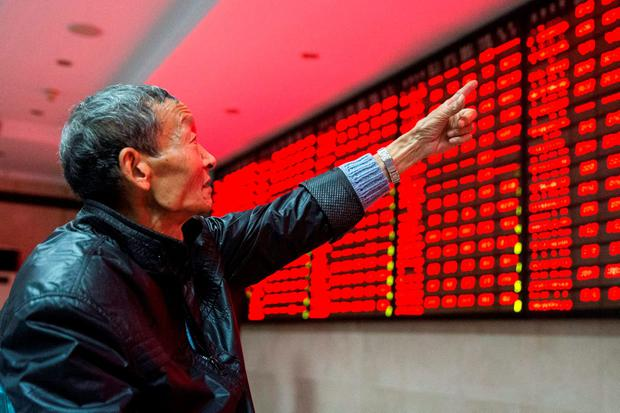 An investor points to an electronic board showing stock information as he speaks to another investor, at a brokerage house in Nanjing, Jiangsu province, China. Photo: Reuters
