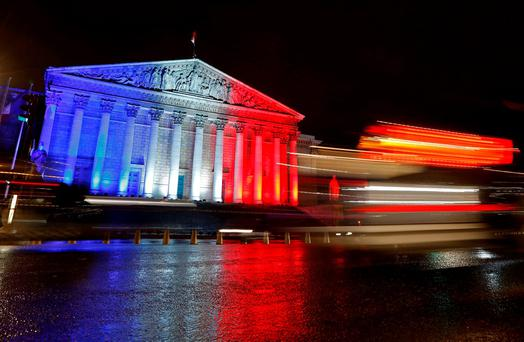 The National Assembly is lit with the blue, white and red colours of the French flag in Paris. Reuters/Jacky Naegelen