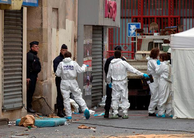 Investigating police officers are pictured outside Saint Denis, near Paris. (AP Photo/Peter Dejong)