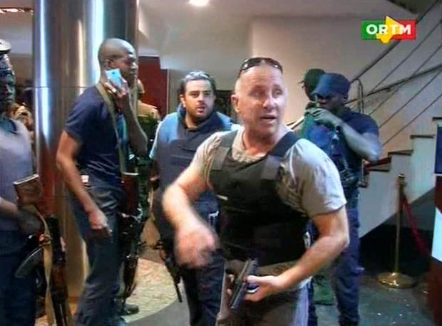 In this TV image taken from Mali TV ORTM, a security officer gives instructions to other security forces inside the Radisson Blu Hotel in Bamako, Mali. (Mali TV ORTM, AP)
