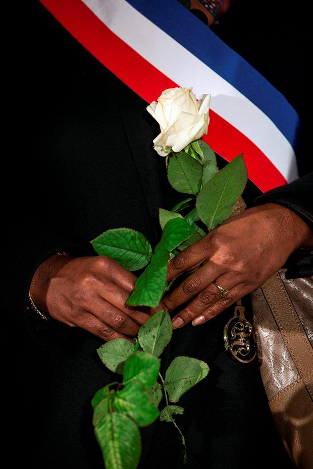 A French politician holds a white rose at a vigil held in Paris Pic:Mark Condren