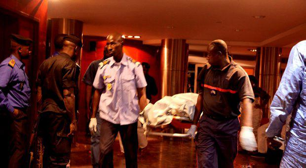 Mali security personal carry the body of a victim inside the Radisson Blu hotel after an attack by gunmen on the hotel in Bamako, Mali, Friday, Nov. 20, 2015