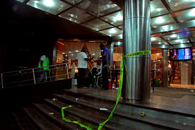 Mali troops, center rear, at the entrance to the Radisson Blu hotel with yellow Police tape around a pillar, right, after an attack by gunmen on the hotel in Bamako, Mali, Friday, Nov. 20, 2015
