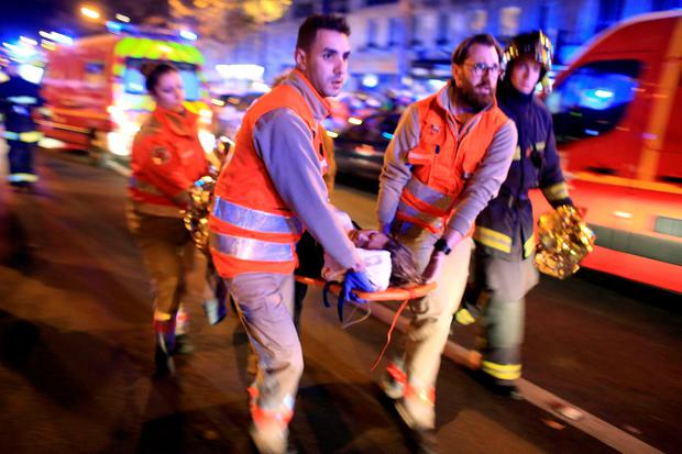 A woman is being evacuated from the Bataclan concert hall after a shooting in Paris