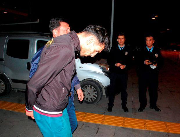 The 26-year old Belgian citizen Ahmet Dahmani is escorted by a plain clothes police officer on November 20, 2015 in Antalya. Photo: AFP/Getty Images