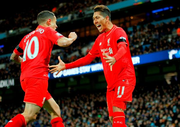 Liverpool's Roberto Firmino and Philippe Coutinho celebrate after Manchester City's Eliaquim Mangala scored an own goal